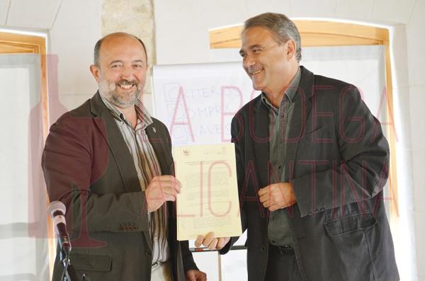 Juan Cascant (izq.) y Juan José Ruiz presentan el documento de la firma del convenio de colaboración entre Celler la Muntanay y la UMH. /LBA